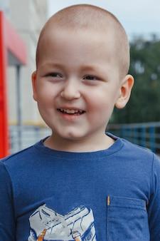 青いシャツ、屋外ショットでかわいい笑顔の小さな男の子の肖像画