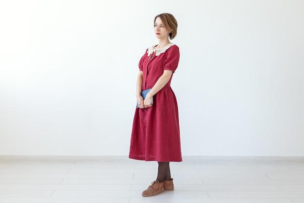 手に古典的な本を保持しているドレスのかわいい笑顔の控えめな女性の肖像