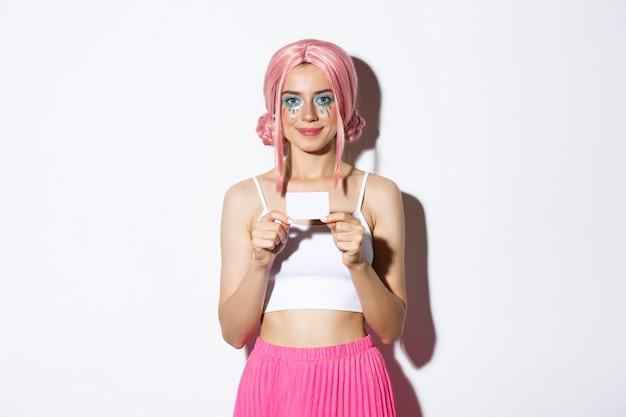 ピンクのかつら、クレジットカード、白い背景の上に立っているかわいい笑顔のパーティーの女の子の肖像画