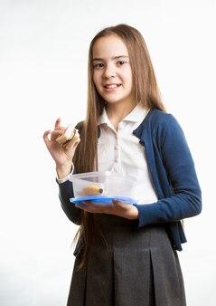 白い背景に、サンドイッチを保持しているかわいい笑顔の女子高生の肖像画