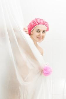 Портрет милой улыбающейся женщины, принимающей душ и смотрящей за занавеской
