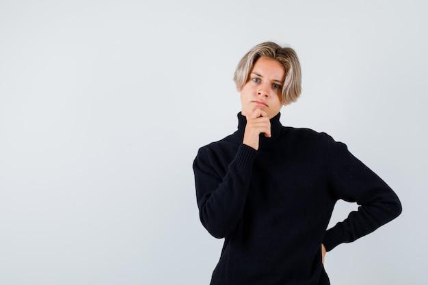 タートルネックのセーターのあごに手を置いて、思慮深い正面図を探しているかわいい十代の少年の肖像画