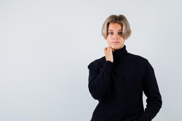タートルネックのセーターで彼の襟に手を置いて、心配そうな正面図を見てかわいい十代の少年の肖像画