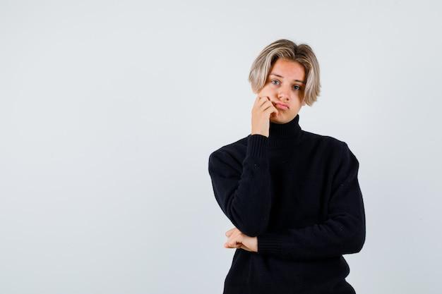 タートルネックのセーターで手に頬を傾けて悲しい正面図を見てかわいい十代の少年の肖像画