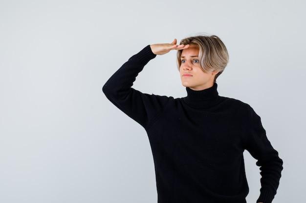 Портрет симпатичного мальчика-подростка, смотрящего вдаль, положив руку на голову в черном свитере с высоким воротом и смотрящего сфокусированным видом спереди