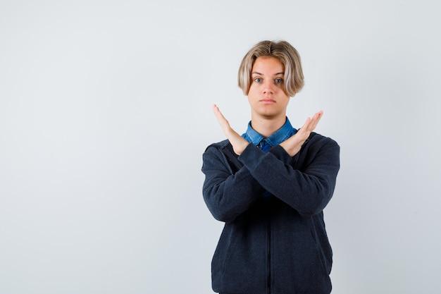 シャツ、パーカー、自信を持って正面から拒否ジェスチャーを示すかわいい十代の少年の肖像画