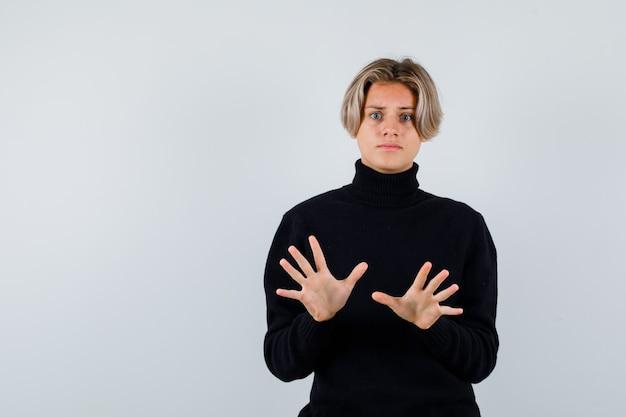 검은 터틀넥 스웨터에 항복 제스처를 보여주는 귀여운 십 대 소년의 초상화와 겁에 질린 전면 보기