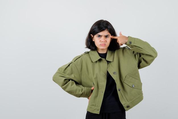 군대 녹색 재킷에 자살 제스처를 보여주는 귀여운 십 대 소녀의 초상화와 우울한 전면 보기