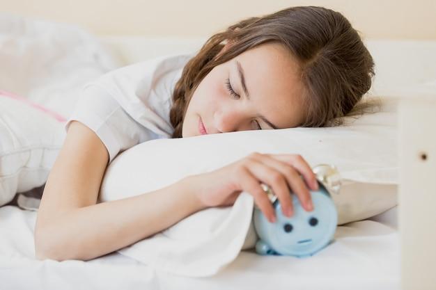 枕の下に目覚まし時計を保持しているかわいい10代の少女の肖像画