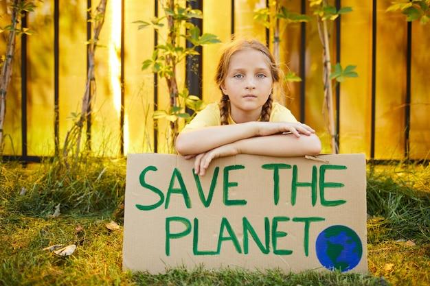 귀여운 십 대 소녀의 초상화 저장 행성으로 기호를 들고 야외에서 자연을 위해 항의하는 동안 카메라를 찾고 공간을 복사