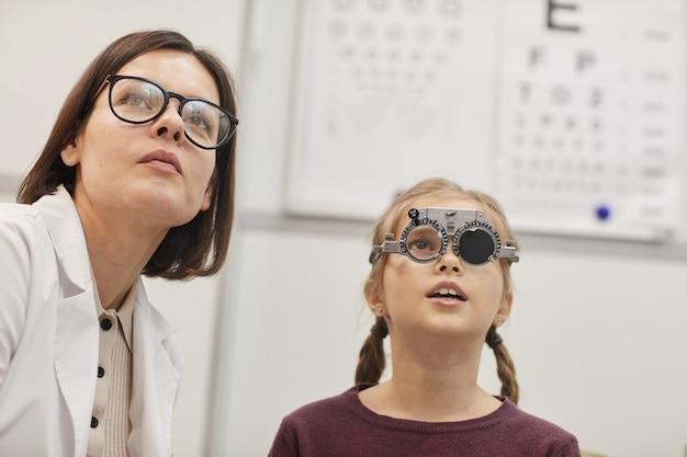 Портрет милой девочки-подростка в пробной оправе во время проверки зрения ребенка