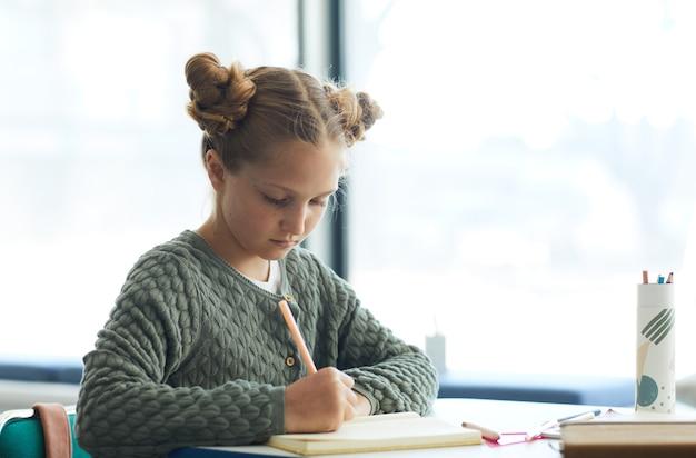 学校の机に座ってノートに書くかわいい10代の少女の肖像画