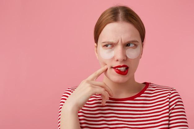 Портрет симпатичной думающей молодой рыжеволосой девушки с красными губами и с пятнами под глазами, одетой в красную полосатую футболку, задается вопросом, какое платье надеть. стенды.
