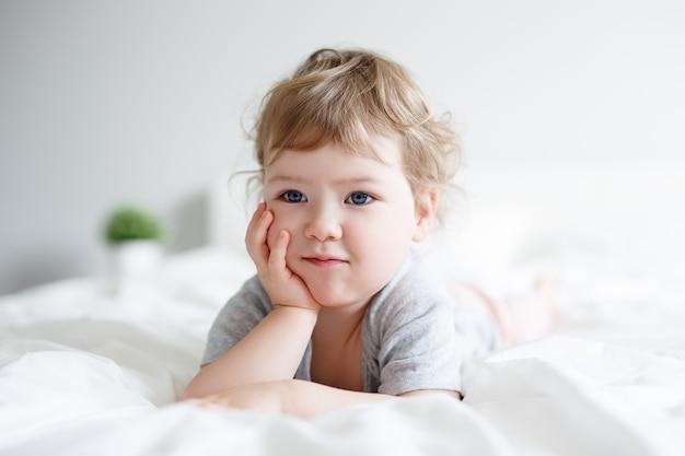 ベッドに横になって何かを夢見てかわいい思いやりのある少女の肖像画