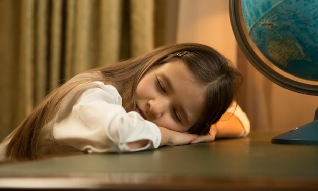 机の上で寝ているかわいい疲れた女子高生の肖像画