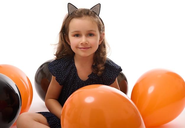 Портрет милой девушки ведьмы в платье и обруче на хэллоуин с кошачьими ушами, весело проводящими время с красочными черными и оранжевыми воздушными шарами, изолированными на белом фоне с копией пространства. хэллоуин вечеринка.