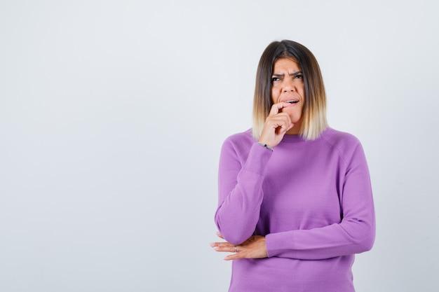 指を噛んで、紫色のセーターで見上げて、困った正面図を見てかわいい女性の肖像画