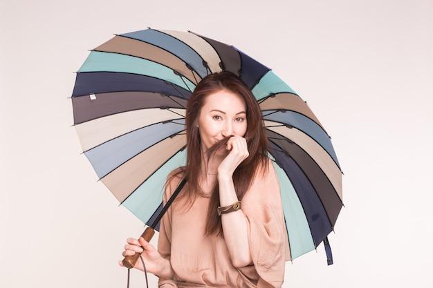 Портрет милой женщины под полосатым зонтиком на белом