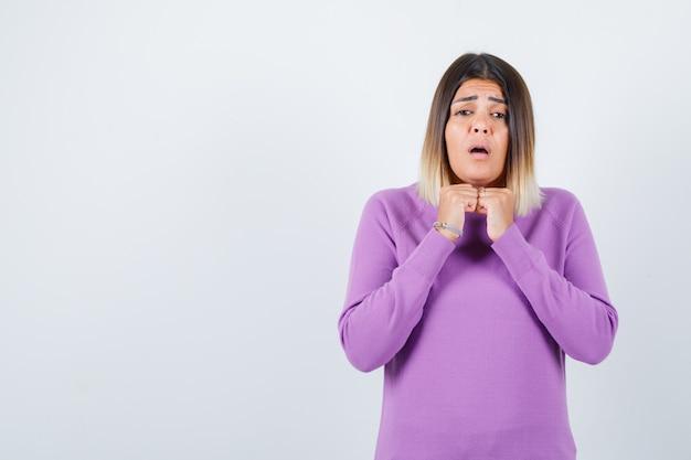 紫色のセーターのあごの下に手と困惑した正面図を探しているかわいい女性の肖像画