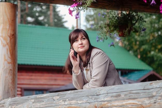 Портрет милой молодой коммерсантки, звонящей по телефону открытой террасе загородного дома. трудоголик женщина в домашней повседневной одежде, работает в сельских районах. творческое вдохновение и начинающий бизнес. копировать пространство