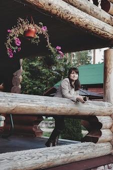 Портрет милой молодой коммерсантки на открытой террасе деревянного дома. красивая женщина в домашней повседневной одежде, идущей по сельской местности. творческое вдохновение и начинающий бизнес. копировать пространство