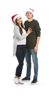 Портрет милой молодой пары в шляпах санта-клауса на белом
