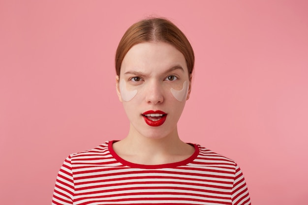 빨간 입술과 눈 밑에 패치가있는 귀여운 젊은 불만이있는 빨간 머리 아가씨의 초상화는 빨간 줄무늬 티셔츠를 입고 입을 크게 벌리고 눈썹을 올립니다.