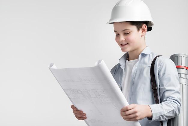 Портрет милого молодого инженера, читающего план строительства