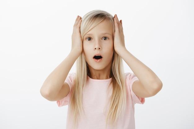 カジュアルな服装でブロンドの髪とかわいい若いヨーロッパの子供の肖像画、頭に手を繋いでいるとショックと驚きから顎を落として、灰色の壁に気絶して立っています。