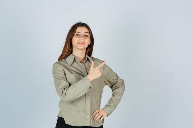 Портрет милой молодой женщины, указывающей на верхний правый угол в рубашке и гордо смотрящей спереди