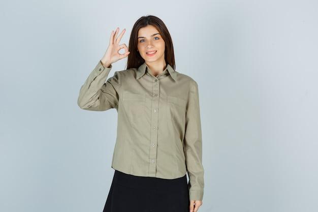 シャツ、スカート、嬉しい正面図でokジェスチャーを示すかわいい若い女性の肖像画