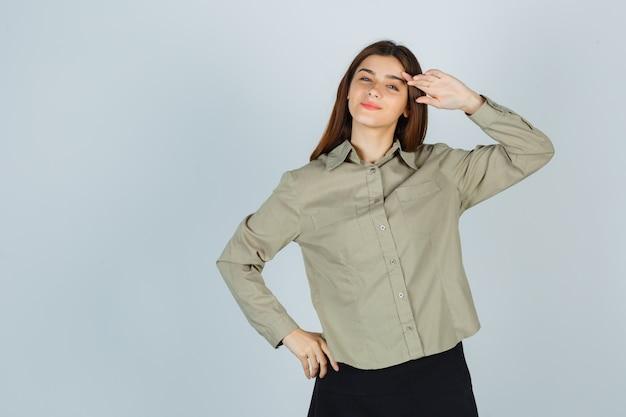Портрет милой молодой женщины, показывающей жест салюта в рубашке, юбке и гордо смотрящей спереди