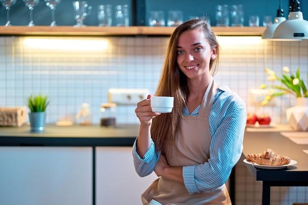 Портрет милой молодой счастливой улыбающейся женщины в фартуке, держащей белую чашку на кухне-чердаке во время перерыва на кофе