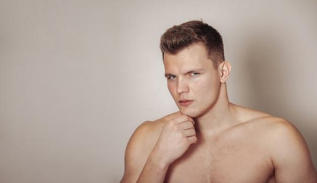 Портрет милого молодого человека спортивной сборки на светлом изолированном фоне. красивый, мускулистый мужчина