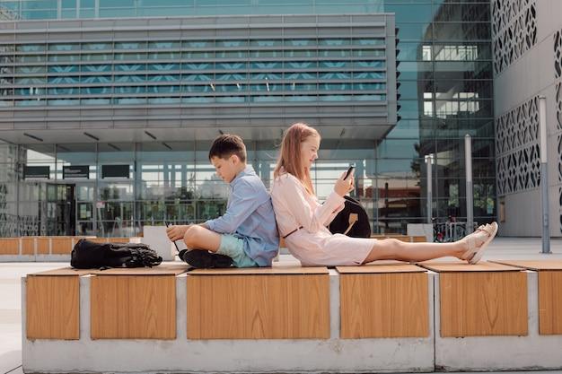 カジュアルを着て、背中合わせに座って、モバイルデバイスを手に持って、スクリーンを真剣に見て、キャンパスの近くの校庭を着ているかわいい若い学生の肖像画
