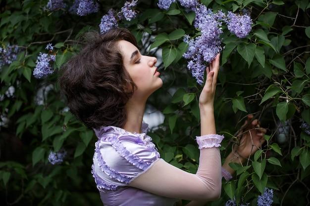 귀여운 젊은 여자와 라일락 부시의 초상화