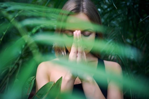 Портрет милой молодой женщины размышляя и делая namaste рука в джунглях.