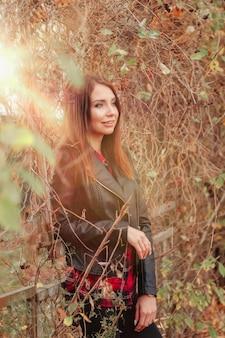 Портрет милой молодой женщины славянской внешности в повседневной одежде осенью, в сельской местности на фоне осеннего парка. симпатичная женщина, идущая в лесу в золотой осени. копировать пространство