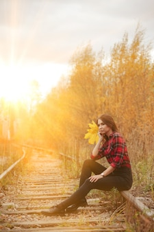 Портрет милой молодой женщины славянской внешности в повседневной одежде осенью, на железной дороге на фоне осеннего парка и реки. симпатичная женщина, идущая в лесу в золотой осени. копировать пространство