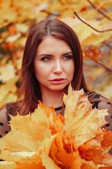 Портрет милой молодой женщины славянской внешности с листьями в повседневной одежде осенью, стоя на фоне осеннего парка. симпатичная женщина, идущая в парке в золотой осени. копировать пространство