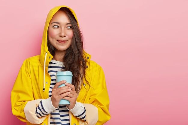 귀여운 젊은 여자의 초상화는 비옷을 입고, 뜨거운 음료로 따뜻해지며, 행복하게 옆으로 보이며, 루즈 뺨에 보조개가 있습니다.
