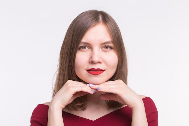 白い背景の上の彼女のあごに赤い唇と手を持つかわいい若い女性の肖像画