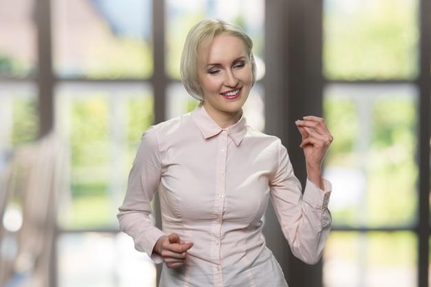 Портрет танцующей коммерсантки. привлекательная европейская женщина улыбается и танцует. большое окно на заднем плане. Premium Фотографии