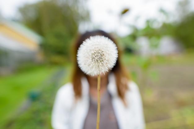 ぼやけたように春の若い女性に咲くタンポポの花の肖像画