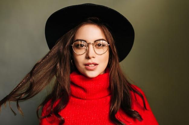 赤いセーターと灰色の壁につばの広い帽子をかぶった黒髪の白人女性の肖像画。