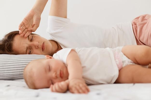 흰색 캐주얼 티셔츠를 입은 검은 머리 여성의 초상화는 어린 딸과 함께 침대에 누워 있고, 실내에서 포즈를 취하고 있으며, 피곤한 표정으로 어린 소녀를 바라보는 여성의 초상화.