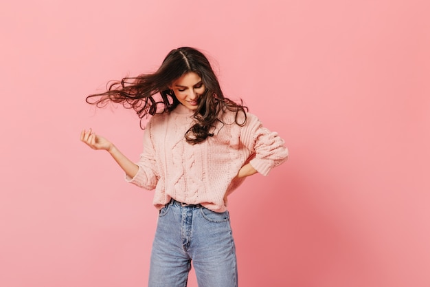 髪を再生する元気いっぱいの黒髪の少女の肖像画。セーターとジーンズの女の子はピンクの背景で楽しんでいます。