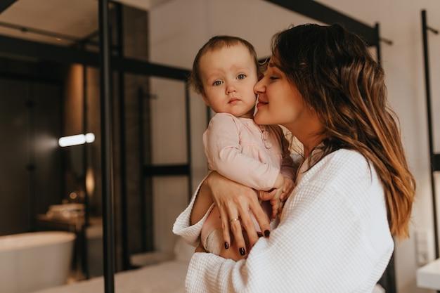 白い家庭服を着た黒髪の母親の肖像画、愛を込めて彼女の小さな金髪の娘を抱き締めます。