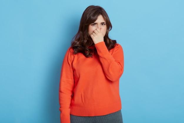 青い壁に隔離された、においにうんざりしている、オレンジ色のジャンパーで鼻をつまんでいる黒髪の女性の肖像画。