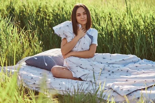 초원에서 부드러운 침대에 앉아 담요를 껴안은 즐거운 외모를 가진 검은 머리 여자의 초상화